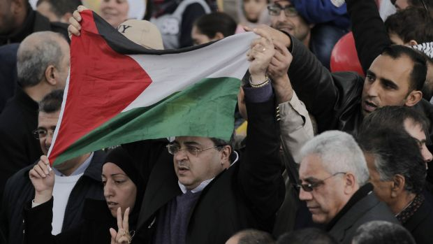 Ahmed Tibi, centre, an Israeli MP, flies the Palestinian flag in the al-Aqsa mosque compound during the ceremony marking ...