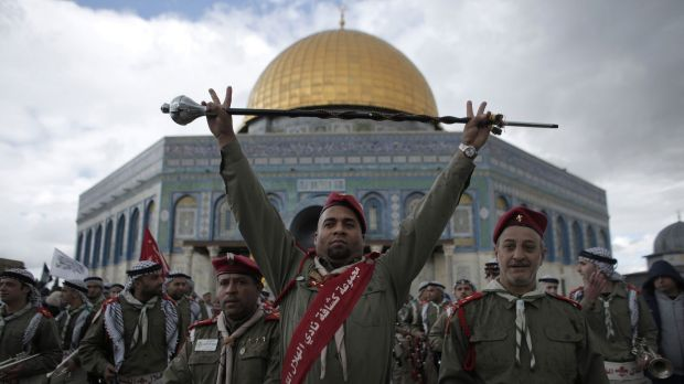 A member of the Palestinian scouts raises a baton during a ceremony to commemorate the birth of the Prophet Muhammad ...