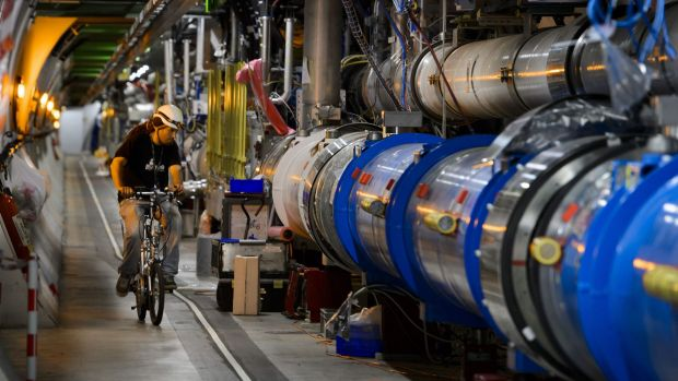 A worker rides a bicycle during maintenance checks at CERN's Large Hadron Collider.