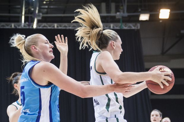 Lauren Jackson of the Canberra Capitals and Penny Taylor of the Dandenong Rangers vie for the ball.