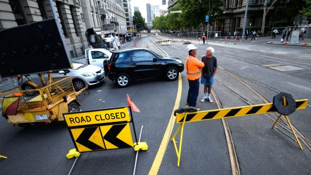 Closed: Workers build a new tram stop near the corner of Flinders and Spencer streets, causing traffic chaos.