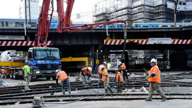 Workers build a new tram stop near the corner of Flinders and Spencer streets.