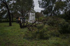 Workers drain a flooded Parkes Way next to a broken tree branch after Monday's thunderstorm.