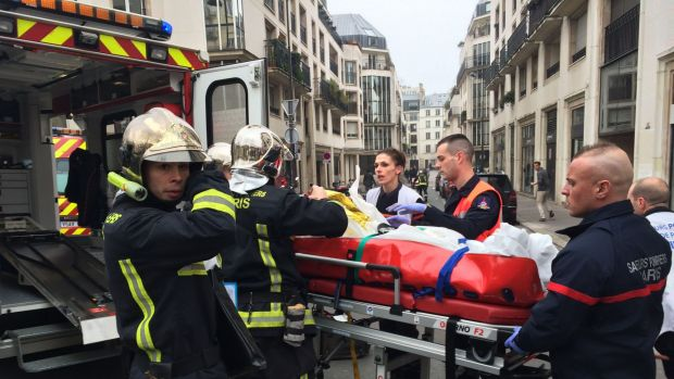 Firefighters carry an injured man on a stretcher from the offices of the French satirical newspaper <i>Charlie Hebdo</i> ...