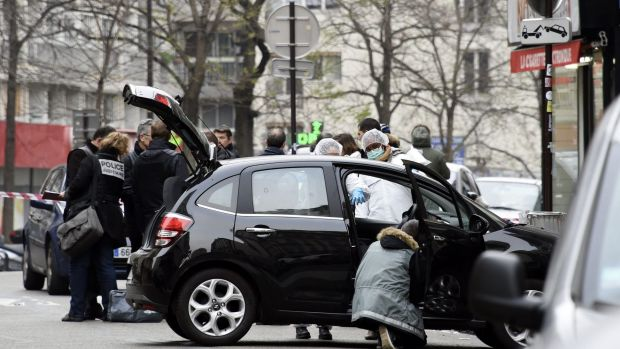 French police officers and forensic experts examine the car used by armed gunmen who stormed the Paris offices of ...