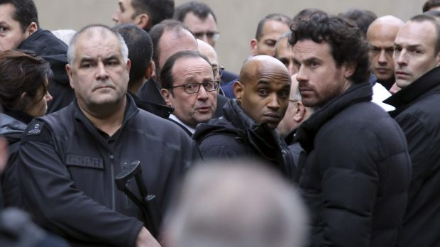 French President Francois Hollande, centre, flanked by security forces arrives at the office of satirical magazine ...