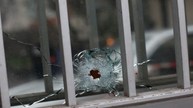 A bullet hole is seen in a window of a building next to the French satirical magazine Charlie Hebdo's office, in Paris.