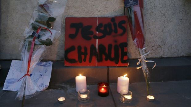 """Flowers, candles and a placard which reads """"I am Charlie"""" at a gathering at the Place de la Republique in Paris."""