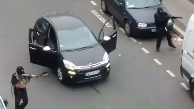 Gunmen flee the offices of French satirical newspaper Charlie Hebdo.