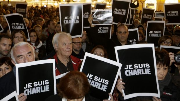 "People hold posters reading ""I am Charlie"" as they gather to express solidarity with those killed in an attack at the ..."