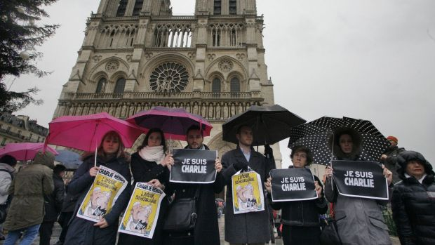 "People hold signs reading '""e suis Charlie"" (I am Charlie) as they stand under the rain with umbrellas in front of ..."