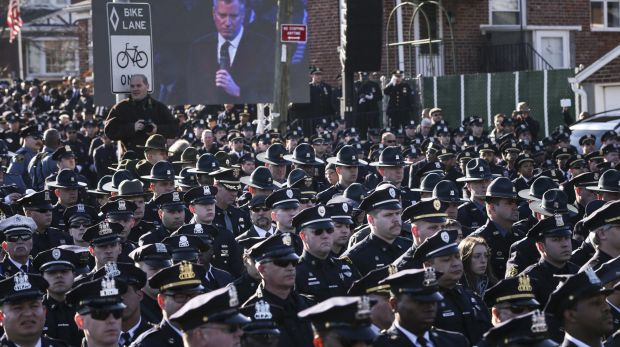 Cold shoulder: Police officers turn their backs on a live video monitor showing New York City Mayor Bill de Blasio as he ...