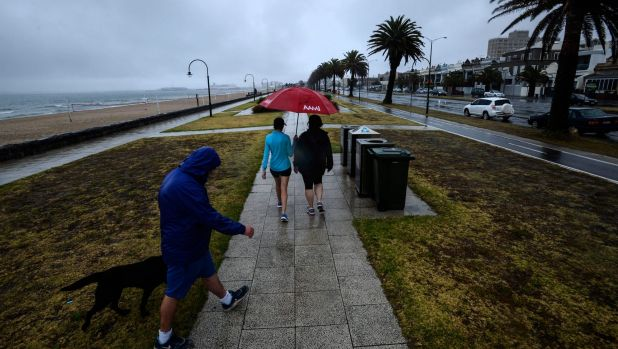 Heavy rain hits Melbourne: pedestrians in South Melbourne.