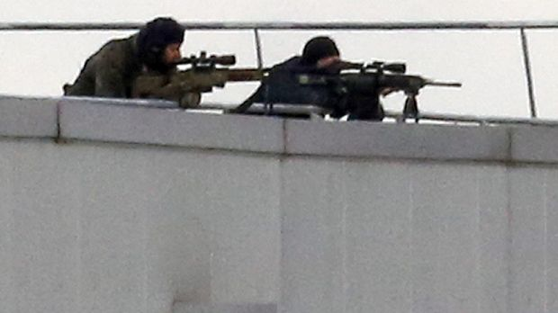 Before the assault ... French special forces take position with sniper rifles on the rooftop of a complex at an ...