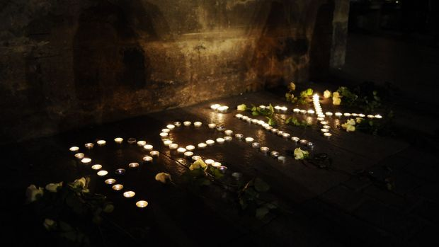 "Lit candles forming the word ""peace"" in French are layed outside the Capitole building in Toulouse, southern France."