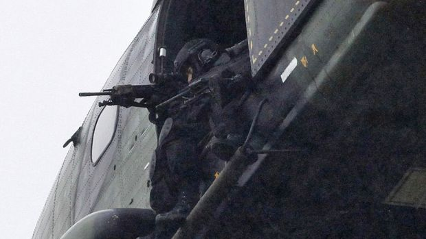 Armed security forces hover in helicopters over the printer business in Dammartin-en-Goele.