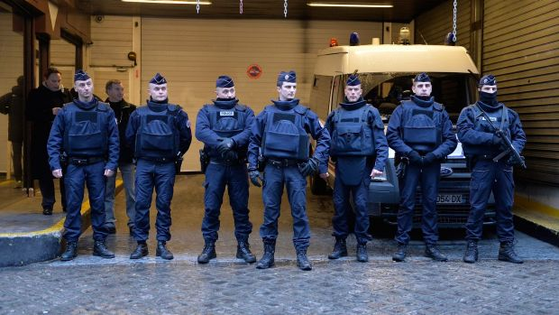 Police stand guard outside the offices of French daily newspaper Liberation as the remaining members of the Charlie ...