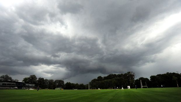 Dark clouds loom on ANU North Oval before it pelted down with rain on Saturday.