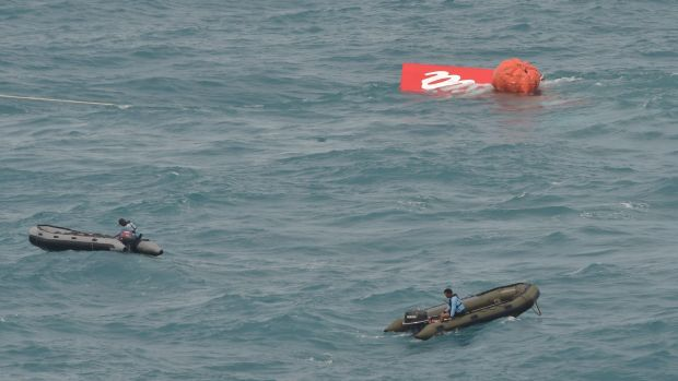 Part of the tail of AirAsia flight QZ8501 floats on the water's surface.