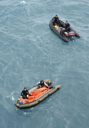 Crew members from an Indonesian navy vessel prepare to conduct operations to lift the tail of AirAsia QZ8501 in the Java sea.