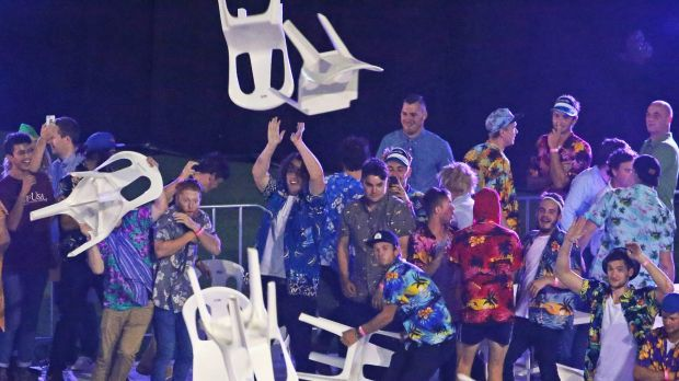Spectators throw plastic chairs.