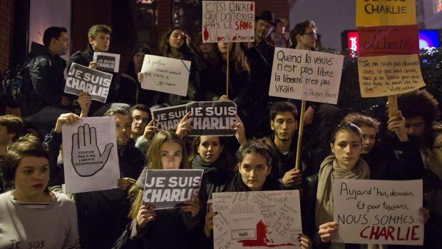 """People hold up """"Je Suis Charlie"""" and other placards at a vigil outside The French Institute in London on Friday."""