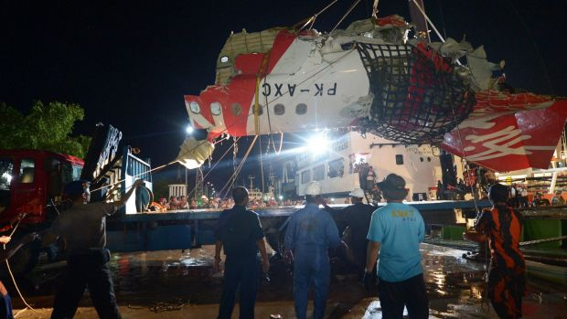The tail section of the Air Asia  flight QZ8501 is prepared to be loaded onto a truck at port in Kumai, Indonesia.