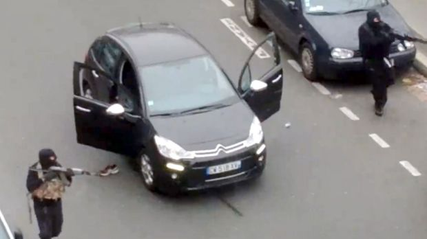 A frame grab taken from footage posted by Jordi Mir shows hooded gunmen aiming rifles towards a police officer.