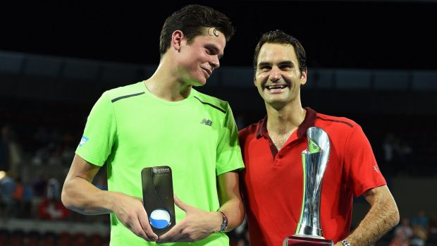 Milos Raonic and Roger Federer with their trophies after the Brisbane International final.
