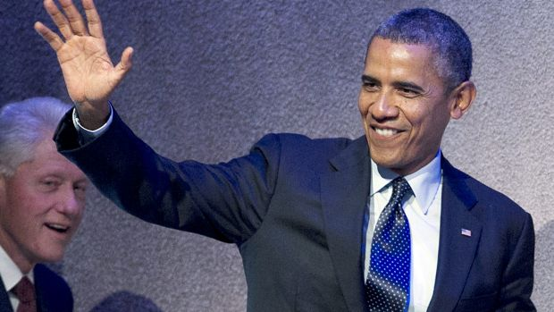 Judging legacies: President Barack Obama waves to a crowd at an event while former president Bill Clinton looks on.