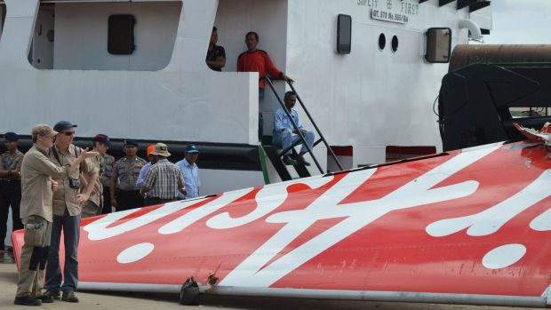 Foreign investigators examine the tail of the AirAsia flight QZ8501 in Kumai on Monday after debris from the crash was ...