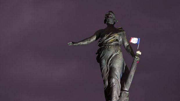 "A French national flag and flowers remain hung at the statue named ""Le triomphe de la Republique"" in Paris."