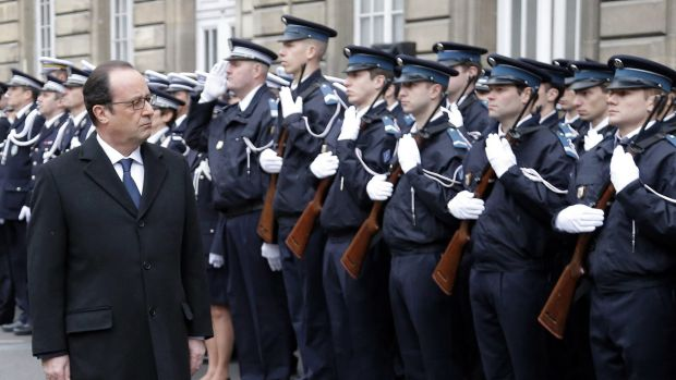 French President Hollande reviews a police honour guard at the Paris prefecture during a ceremony to pay tribute to the ...
