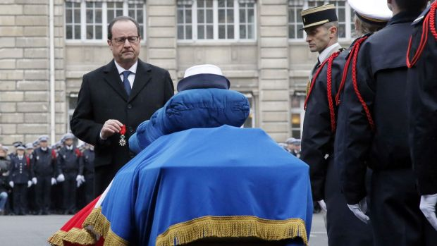 French President Francois Hollande holds the Legion of Honour medal in front of the coffin of French Police officer ...