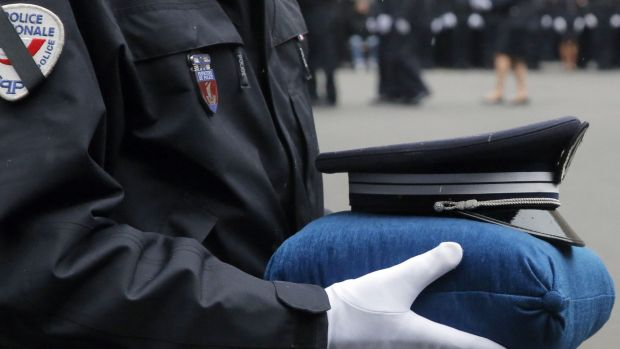 A French police officer holds the hat of late police officer Ahmed Merabet. Police officers Merabet, 40, and Franck ...