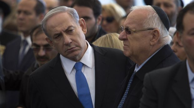 Israeli Prime Minister Benjamin Netanyahu (left) attends the funeral service in Jerusalem of the four Jews killed in an ...