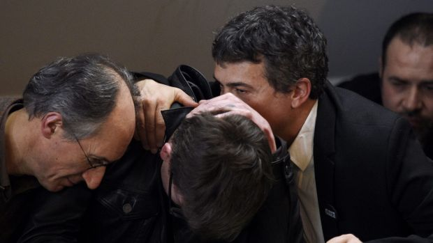 French cartoonist Renald Luzier (centre) is comforted by Charlie Hebdo Editor-in-Chief Gerard Briard (left) and ...