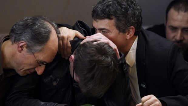 French cartoonist Renald Luzier is comforted by the Editor in Chief of <i>Charlie Hebdo</i>, Gerard Briard (left) and ...