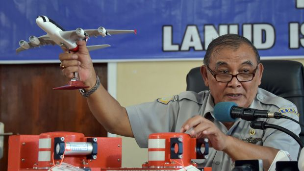 Tatang Kurniadi, the head of the National Transportation Safety Committee, with the flight data recorder (on right of ...