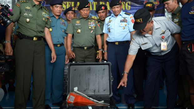 Tatang Kurniadi (right), from The National Transportation Safety Committee, examines the Flight Data Recorder in ...