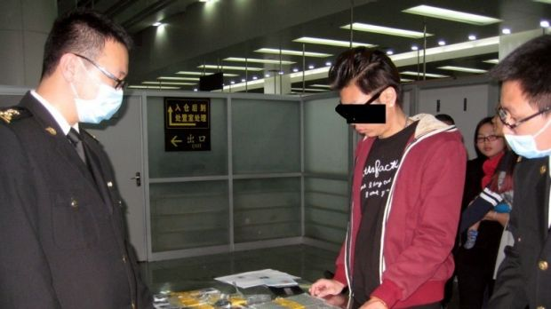 Chinese customs officers confiscate the 94 Apple iPhone smartphones smuggled by a man from Hong Kong, centre, at ...