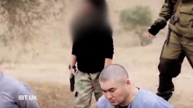 A screenshot from a new video posted online by Islamic State that purports to show a child executing two hostages.