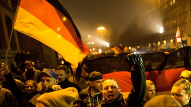 A supporter of the PEGIDA movement holds a flag while supporters gather for a march in their first Berlin demonstration, ...
