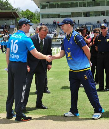 Centre, Prime Minister Tony Abbott during the coin toss as England Captain Eoin Morgan and PM's XI Captain Chris Rogers ...