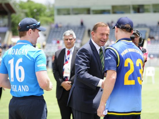 Prime Minister Tony Abbott shakes hands with  PM's XI Captain Chris Rogers.