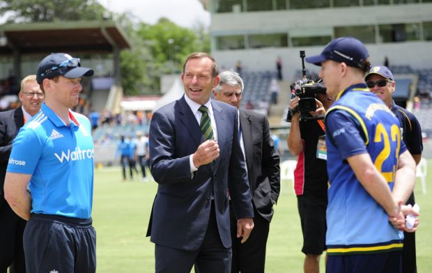 Prime Minister Tony Abbott doing the coin toss whilst from left, England Captain Eoin Morgan and PM's XI Captain Chris ...
