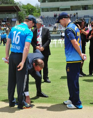 Prime Minister Tony Abbott during the coin toss as England Captain Eoin Morgan and PM's XI Captain Chris Rogers look on.