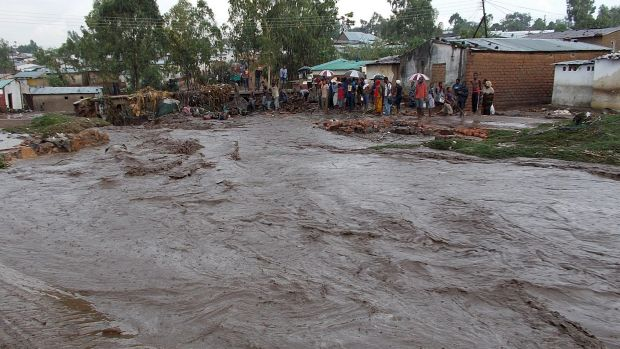 Villagers watch their street flood.