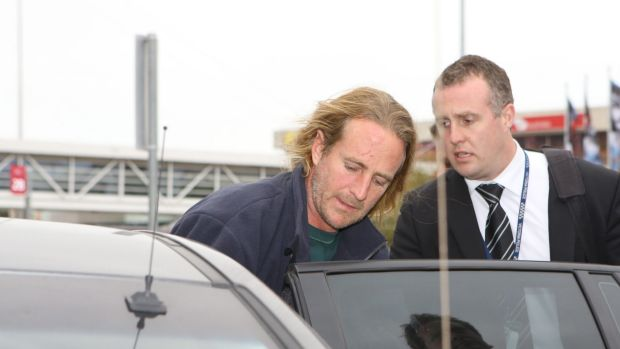 Scott Allen Miller being escorted by police after he was extradited from NSW in July.