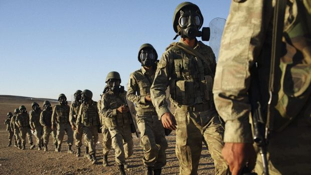 Turkish soldiers secure an area on the border with Syria, where just a few hundred metres away IS militants fired shells ...